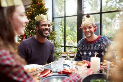 Gay Male Couple Enjoying Christmas Dinner Fooling Around With Table Decorations