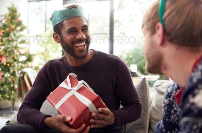 Gay Male Couple At Home Exchanging Gifts On Christmas Day Together