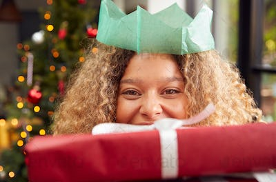Portrait Of Woman Wearing Paper Hat Carrying Pile Of Christmas Presents Standing By Tree At Home
