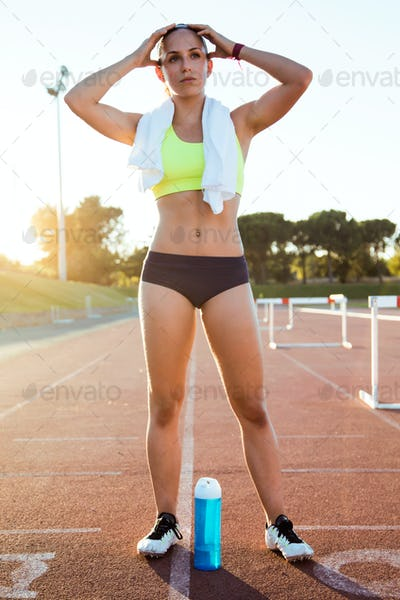 Fit young woman relaxing after run on stadium race track.