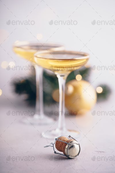 Two champagne glasses,cork and Christmas decorations, close up