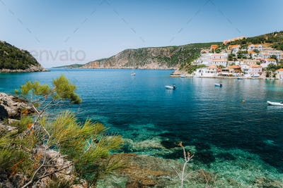 Turquoise transparent lagoon surrounded by green pine trees. Assos village, Kefalonia Greece. Blue