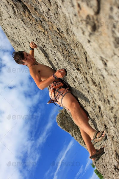 Climber on a rock on the sunset background