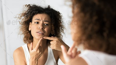 Afro Girl Squeezing Pimple Looking In Mirror In Bathroom, Panorama