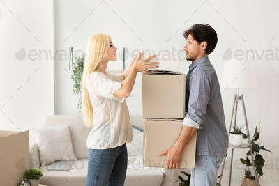 Young Husband And Wife Holding And Packing Moving Boxes Indoor