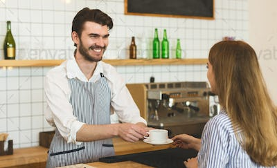 Waiter giving aromatic coffee to girl and widely smiling to her