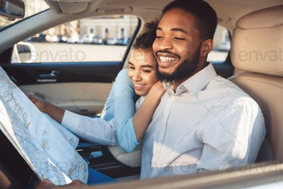 Car trip. Happy afro couple with map in auto