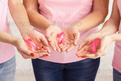 Unrecognizable Breast Cancer Volunteers Holding Pink Ribbons Over White Background