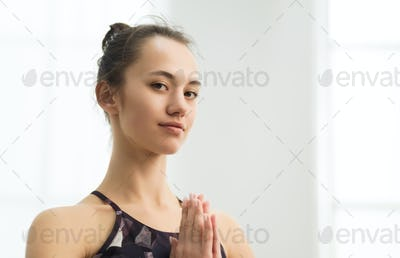 Beautiful woman practising yoga, holding hands in namaste
