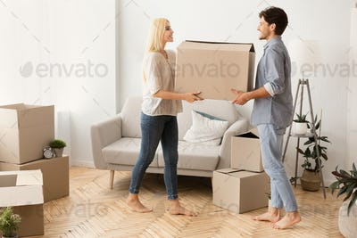 Husband And Wife Carrying Moving Box Together Into New Apartment