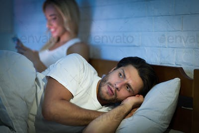 Girlfriend Texting On Phone Lying With Boyfriend In Bed, Low-Light