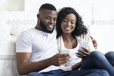 Boyfriend and girlfriend reading messages in each other's cellphones