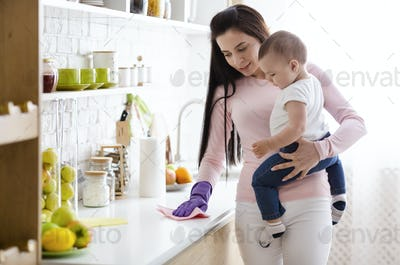 Young mother with baby boy cleaning kitchen at home