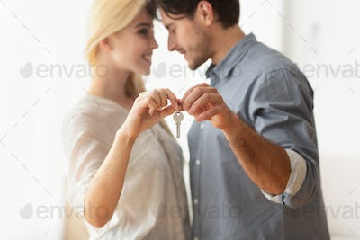 Husband And Wife Holding New Flat Key And Hugging Indoor