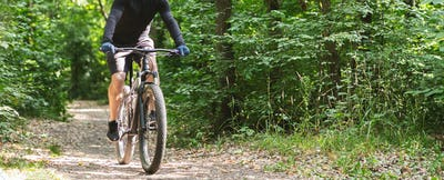 Young athletic cyclist riding down summer woods
