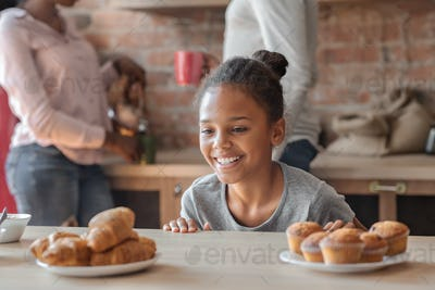 Charming girl looking with joy at sweets at kitchen