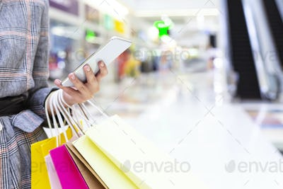 Shopping concept. Woman using smartphone in big mall