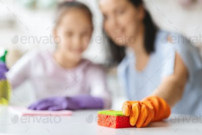 Closeup of little girl helping mother to clean flat