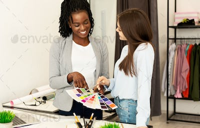 Two Clothing Designers Choosing Colors For New Collection In Workshop