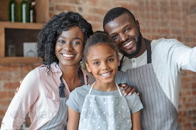 Portrait of happy family posing over kitchen background