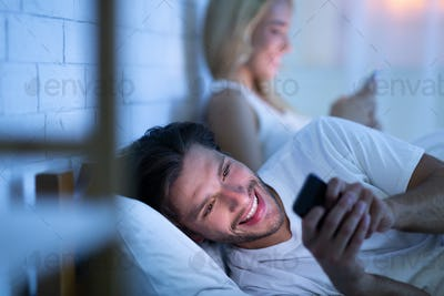 Husband Chatting On Smartphone Lying In Bed With Wife