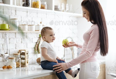 Caring mother offering fresh green apple to her infant at kitchen