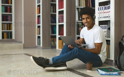 Afro student listening to music while studying, sitting on floor