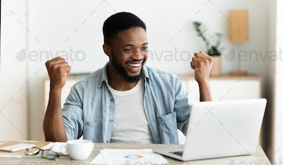 Black employee looking at laptop screen and celebrating success