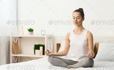 Woman meditating and practising yoga in the morning