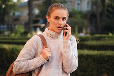 Astonished student girl in sweater with backpack talking on cellphone amazedly looking in camera