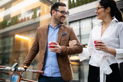 Business people discussing and smiling while walking together outdoor