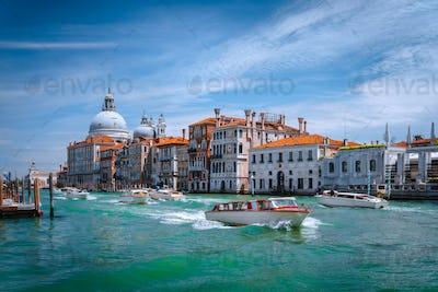 Pleasure tourist boats on Grand Canal and Basilica Santa Maria della Salute, Venice, Italy