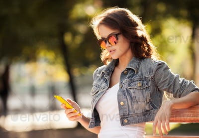 Young Woman Using Smartphone. City Park On Background.