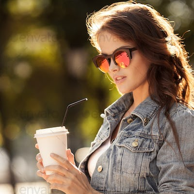 Young Woman Drinking Coffee From Paper Cup. Sitting On Bench
