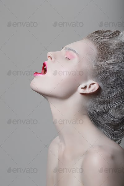 Young female fashion model with eyes closed and opened mouth