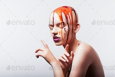 Studio shot of hairless woman with paint on head