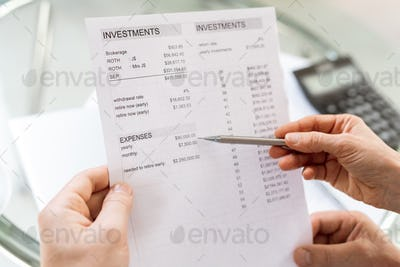 Human hand holding pen while pointing at sum of money in financial document