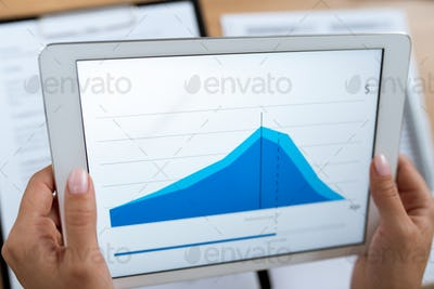 Real estate agent or financial advisor holding tablet with rate change graph