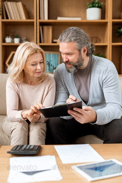 Mature man and woman reading terms of contract while going to buy new house