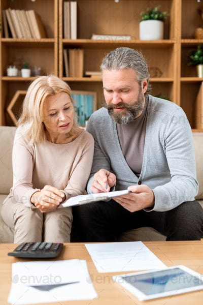 Mature woman listening to her husband pointing at document while reading it