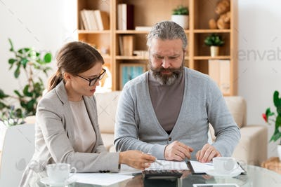 Young confident insurance agent explaining retired man points of the contract