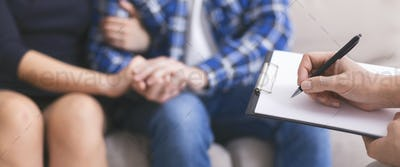 Worried couple holding hands, specialist writing report in notepad