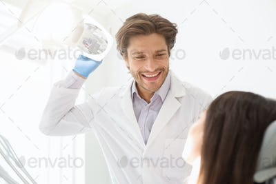Cheerful young dentist greeting his female patient