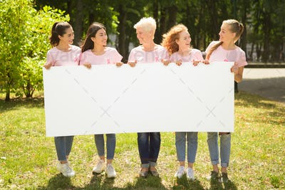 Women In Breast Cancer T-Shirts Holding White Board In Park