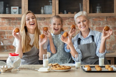 Happy women holding freshly baked cupcakes and smiling