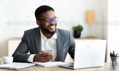 Portrait of smiling black businessman sitting at workplace with cellphone