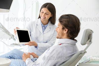 Female dentist doctor showing patient blank digital tablet screen