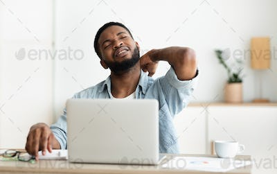 Black man suffering from neck pain while working on laptop