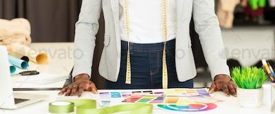 Unrecognizable Dressmaker Choosing Color Samples In Fashion Studio