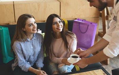 Waiter bring coffee for two cheerful girls in cafe after shopping